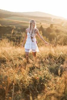 村で休んでいる素朴なスタイルを着ている若いかなり自由奔放に生きるヒッピー女性