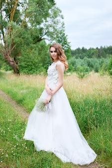 Молодая красивая невеста в белом свадебном платье на открытом воздухе