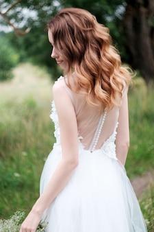 屋外の白いウェディングドレスの若いかわいい花嫁