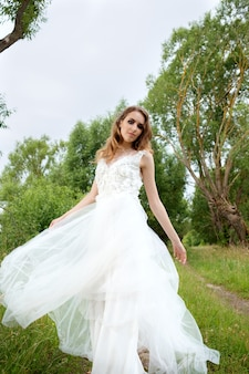 Молодая красивая невеста в белом свадебном платье крутится вокруг
