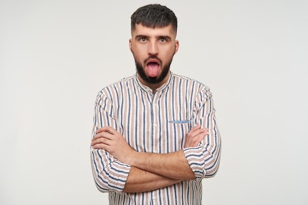 그의 가슴에 손을 접고 흰 벽에 서있는 혀를 보여주는 젊은 예쁜 갈색 눈동자 수염 갈색 머리 남성