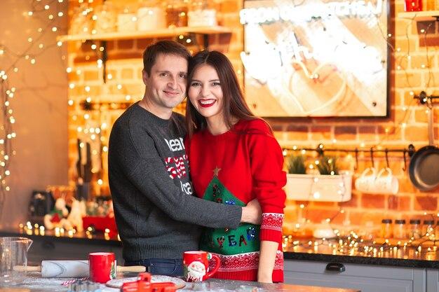 若いかなりブルネットのアジアの女性とクリスマスのセーターの白人男性