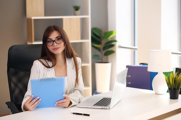 사무실에서 노트북으로 젊은 예쁜 갈색 머리 비즈니스 여자.