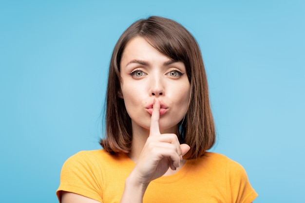 Young pretty brunette female keeping forefinger by her pouted lips while asking to be quiet