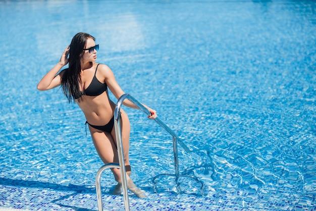 サングラスのプールで黒い水着の若いかなりブルネットの女の子
