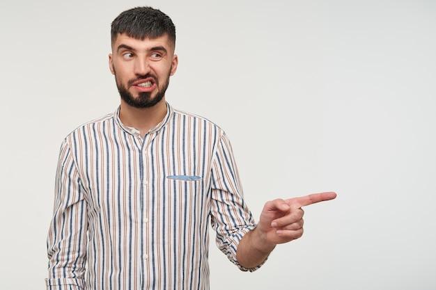 Молодой симпатичный брюнет с бородой, указывая в сторону указательным пальцем и недовольно скручивая рот, изолированный на белой стене