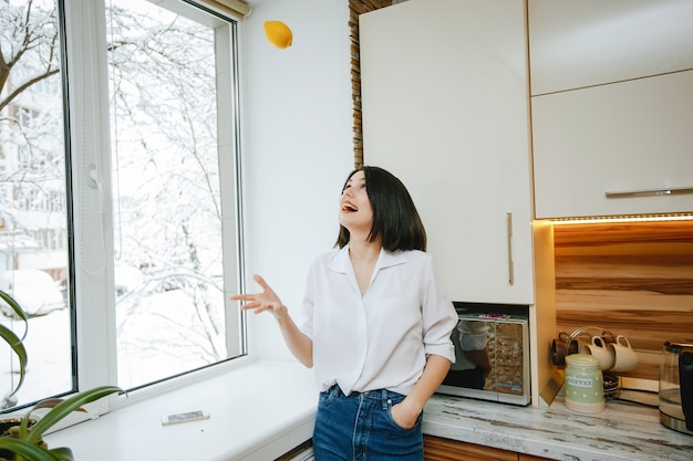 Young and pretty brunette standing by the window in the kitchen with lemon