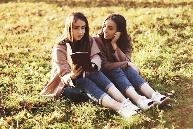Young pretty brunette twin girls sitting on the grass with legs slightly bent in knees and looking in a brown book, wearing casual coat in autumn sunny weather on blurry background.