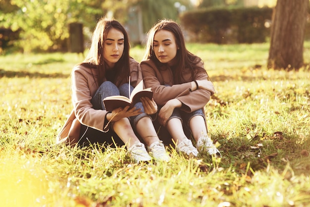 Young pretty brunette twin girls sitting on the grass with legs slightly bent in knees and reading in a brown book, wearing casual coat in autumn sunny parkr on blurry background.