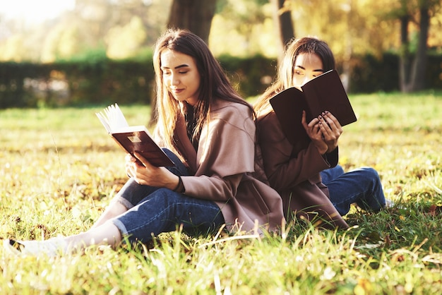Young pretty brunette twin sisters sitting back to back on the grass with legs slightly bent in knees with brown books in hands, wearing casual coat in autumn sunny park on blurry background.