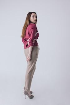 スタイリッシュなカジュアルな服装で後ろからポーズをとって長い髪を持つ若いかなりブルネット