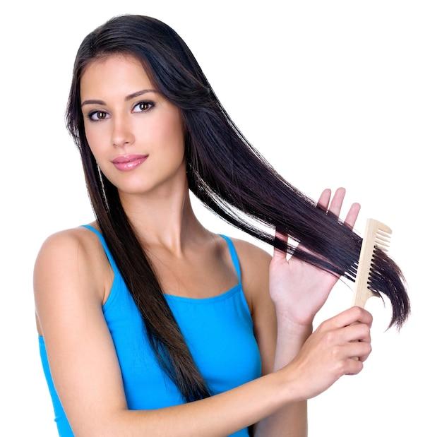 Молодая красивая брюнетка женщина расчесывает свои красивые длинные волосы - isoalted на белом фоне