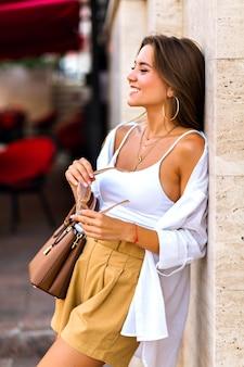 若いかなりブルネットの女性がベージュの大理石の背景でポーズ、リネンベージュのショートパンツ、キャラメルレザーの高級バッグ、白いシャツ、ゴールドのアクセサリーを着ています。ストリートスタイルの衣装。