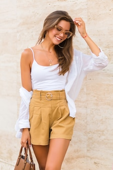 Young pretty brunette woman posing at beige marble background, wearing linen beige shorts, caramel leather luxury bag, white shirt and gold accessories. street style outfit .