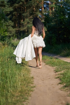 Young pretty brunette woman in white wedding dress, walking in the forest barefoot holding hem of dress , view from back