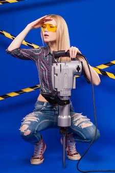 Young pretty builder girl in checkered shirt, jeans and glasses hold puncher
