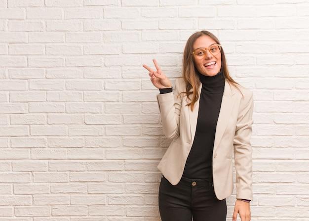 Молодая красивая деловая женщина-предприниматель делает жест победы