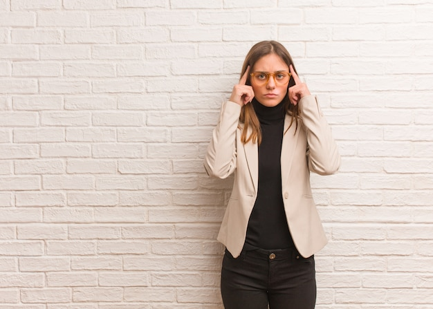 Young pretty business entrepreneur woman doing a concentration gesture