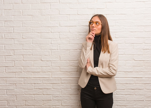 Young pretty business entrepreneur woman doubting and confused