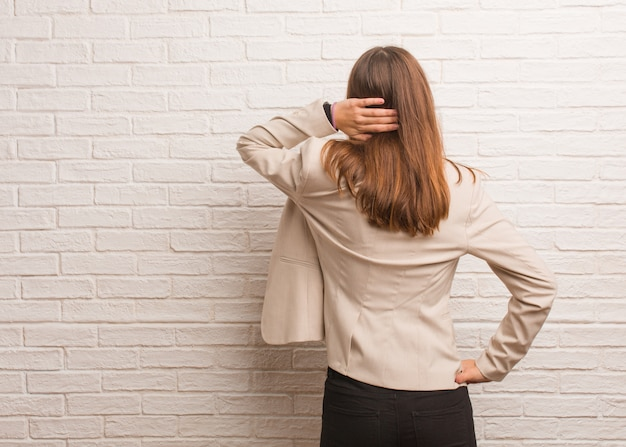 Young pretty business entrepreneur woman from behind thinking about something