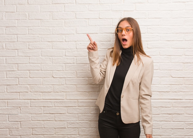 Young pretty business entrepreneur woman pointing to the side