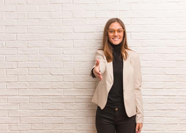 誰かに挨拶するために手を差し伸べる若いかなりビジネス起業家女性
