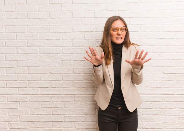Young pretty business entrepreneur woman rejecting something doing a gesture of disgust