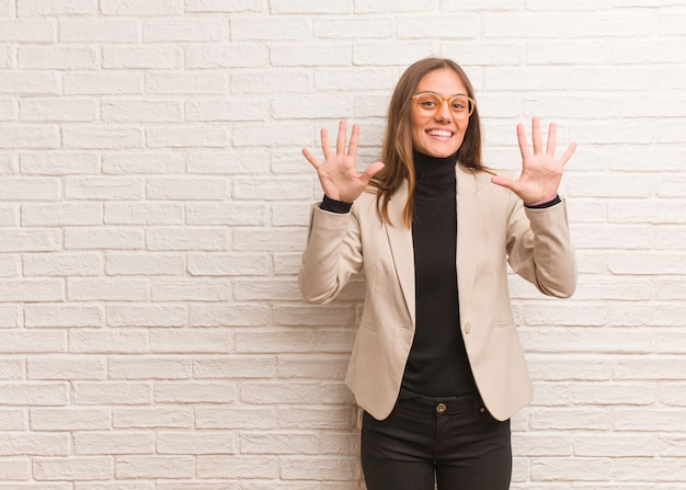 Young pretty business entrepreneur woman showing number ten
