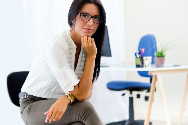 Молодая красивая деловая женщина в ее офисе.