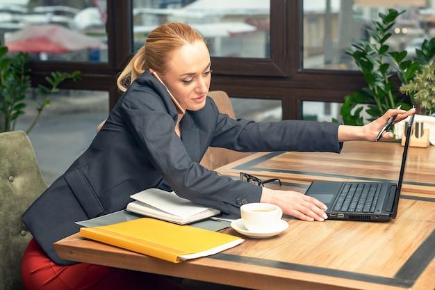 若いかなりビジネスの女性は、オフィスで働くためのスマートフォンと開いているラップトップで話しています。