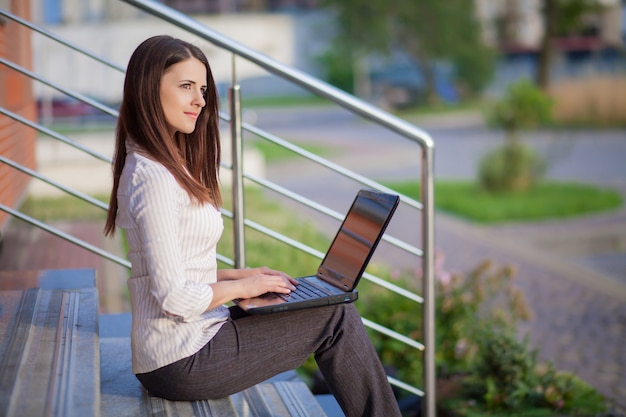 A young pretty business woman outside office building with laptop compute
