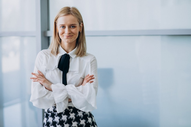Young pretty business woman standing in office