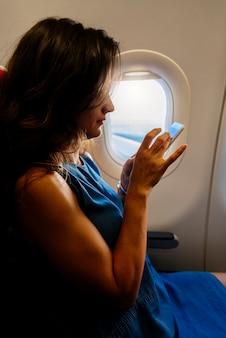 飛行機にモバイルを使用して若いきれいなビジネスウーマン。旅行のコンセプト。