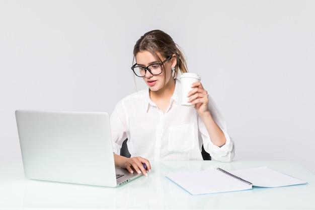 흰색 배경에 고립 된 사무실 책상에서 노트북으로 젊은 예쁜 사업 여자