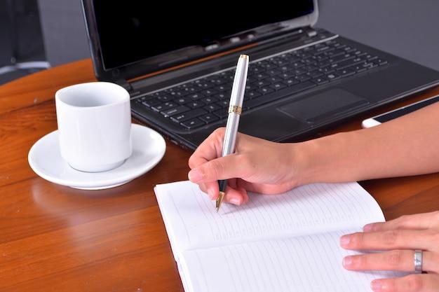 흰색 배경에 고립 된 노트북으로 젊은 예쁜 비즈니스 우먼