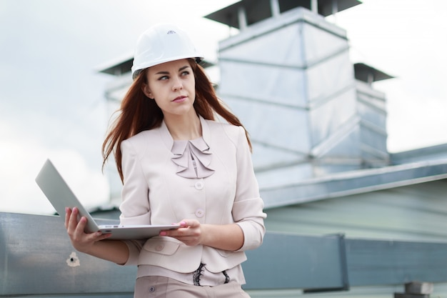 Young, pretty businesswoman in beige suit, brown trousers and helmet sit on the roof and hold laptop