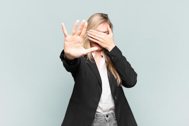 젊고 예쁜 여성 사업가가 손으로 얼굴을 가리고 다른 손을 앞으로 올려 카메라를 멈추고 사진이나 사진을 거부합니다.