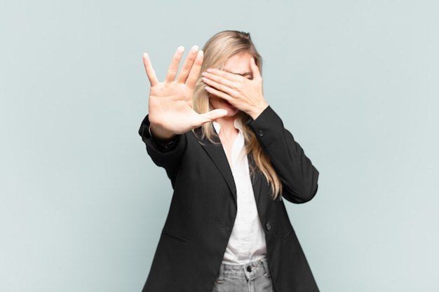 Young pretty businesswoman covering face with hand and putting other hand up front to stop camera, refusing photos or pictures