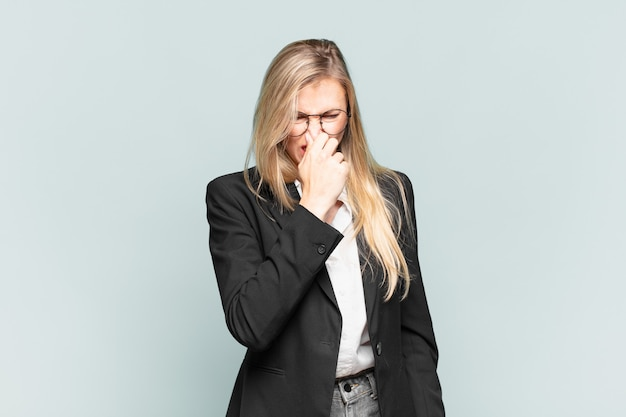 Young pretty businesswoman feeling disgusted, holding nose to avoid smelling a foul and unpleasant stench