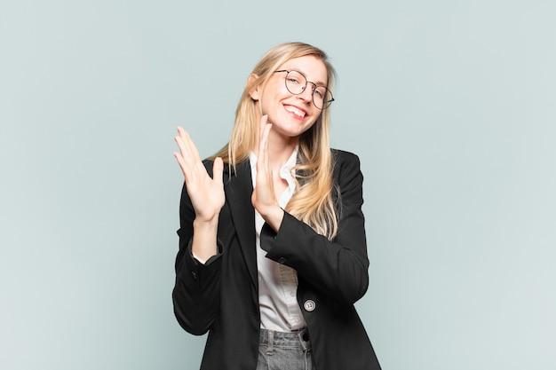 젊고 예쁜 여성 사업가는 행복하고 성공하며 웃고 박수를 치며 박수를 치며 축하합니다