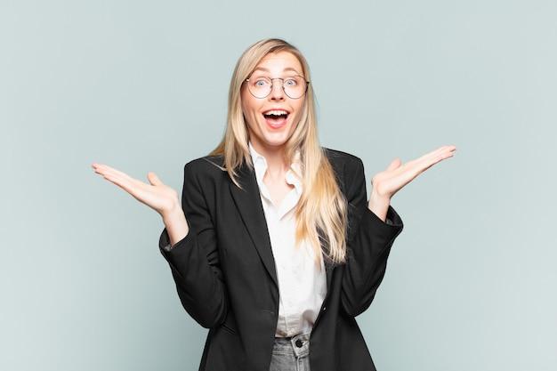 Молодая красивая деловая женщина чувствует себя счастливой, взволнованной, удивленной или шокированной, улыбается и удивляется чему-то невероятному