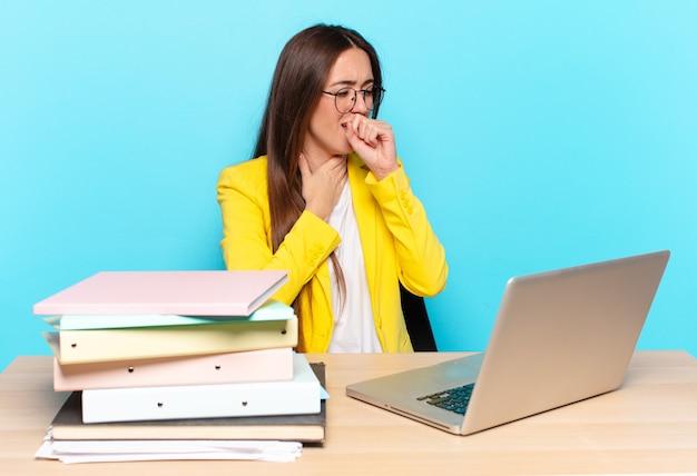 Молодая красивая деловая женщина чувствует себя плохо с симптомами гриппа и болью в горле, кашляет с прикрытым ртом
