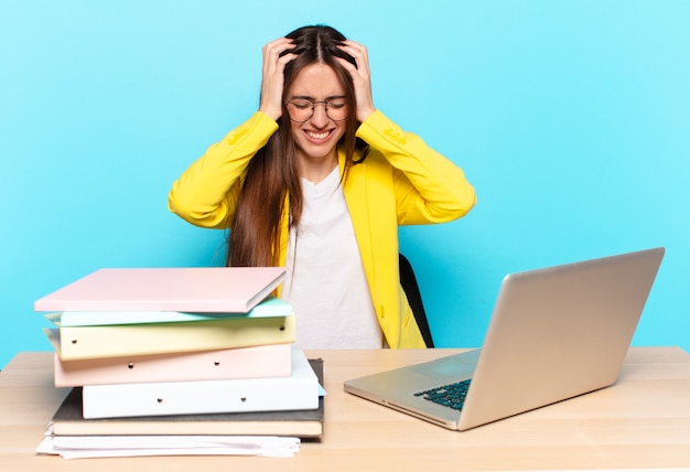 젊은 예쁜 사업가 스트레스와 좌절감을 느끼고, 손을 머리에 올리고, 피곤하고, 불행하고, 편두통을 느낍니다.