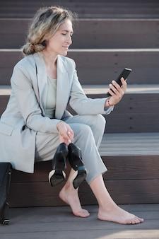 그녀의 굽 높은 신발과 스마트폰을 들고 젊은 예쁜 사업가