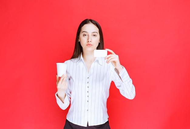 赤い背景にプラスチック製のコップと名刺を保持している若いかわいい実業家。