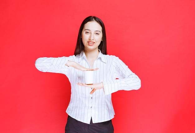Piuttosto giovane imprenditrice azienda bicchiere di plastica su sfondo rosso.