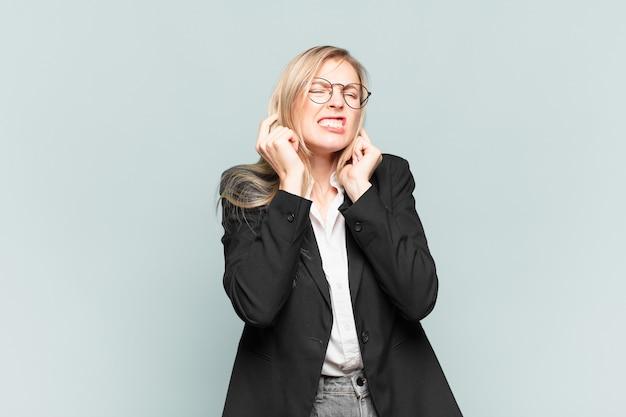 怒り、ストレス、イライラしているように見え、耳をつんざくような音、音、または大音量の音楽で両耳を覆っている若いかわいい実業家