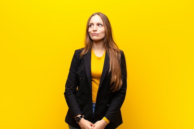 Young pretty businesswoman looking puzzled and confused, wondering or trying to solve a problem or thinking against orange background