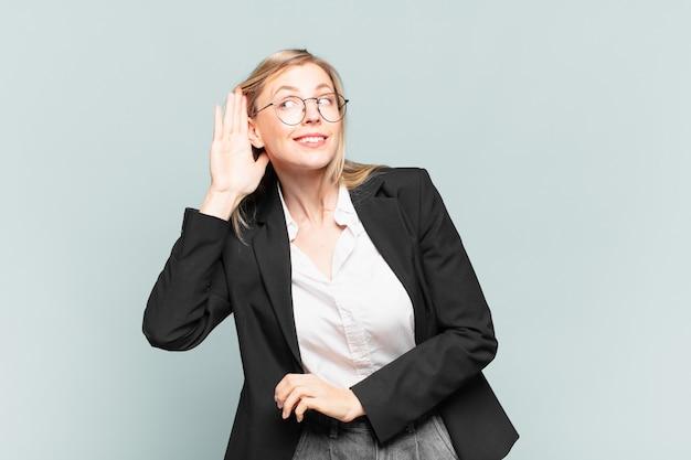 Молодая красивая деловая женщина выглядит серьезной и любопытной, слушает, пытается услышать секретный разговор или сплетню, подслушивает