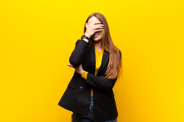 Young pretty businesswoman looking stressed, ashamed or upset, with a headache, covering face with hand against orange